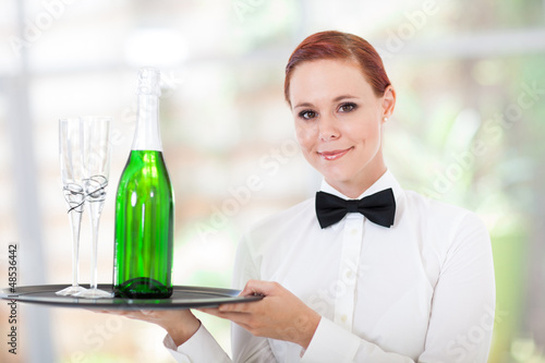 pretty young waitress serving champagne in restaurant