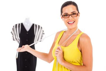 happy female dressmaker presenting a dress on white