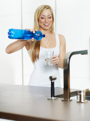 Woman infusing a drinking glass with water in her kitchen
