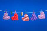 hearts hanging on a clothesline with clothespins, blue backgroun