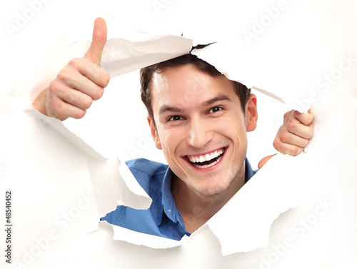 Man with thumbs up peeping through paper hole