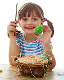 a happy little girl painting easter eggs - white background