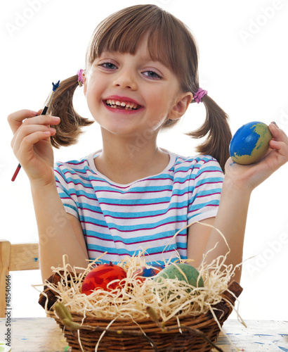 a happy little girl coloring easter eggs - white background