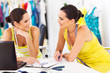 two happy fashion designers discussing new design in studio