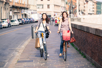 Two Beautiful Women Walking in the City with Bicycles and Bags
