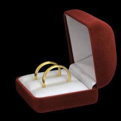 A pair of wedding rings in jewelry box on black background