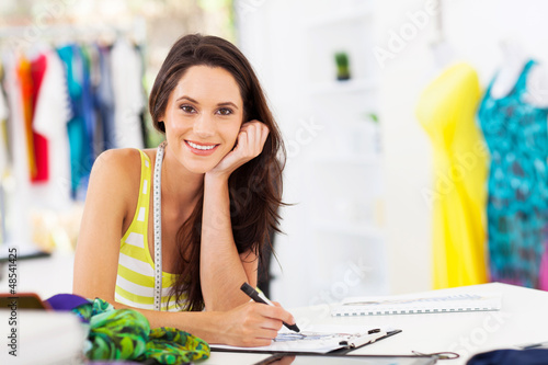 attractive young female dressmaker sketching in studio