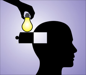 A hand inserting a glowing light bulb into a man's head