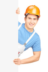 A male worker with helmet posing behind a blank panel