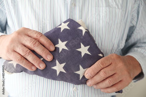 businessman with an old folded USA flag
