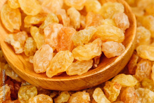 Golden raisins close- up and wooden spoon, food background