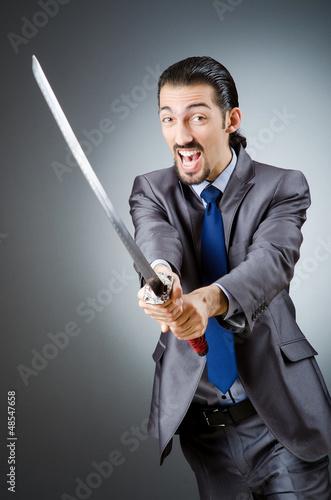 Staande foto Angry businessman with sword in dark room