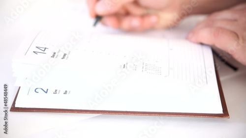 Man writing information in agenda book