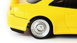 rear wheel of yellow toy radio-controlled car slips on white