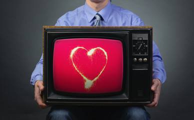 Retro TV featuring sparkling heart in the hands of men.