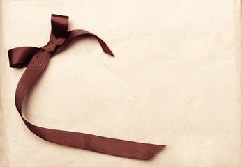 Brown ribbon over vintage gift old paper background