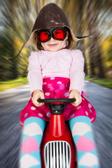 Girl on toy racing car