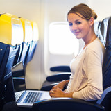 Young woman on her laptop computer on board of an airplane