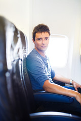 Handsome young man on board of an airplane during flight
