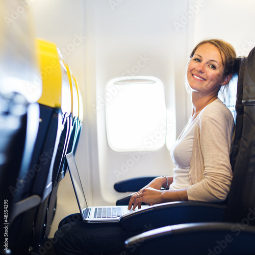 Young woman working on her laptop  on board of an airplane