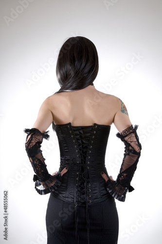 Rear view of a woman in black corset