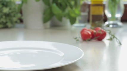 Male chef putting spaghetti onto plate, tracking shot