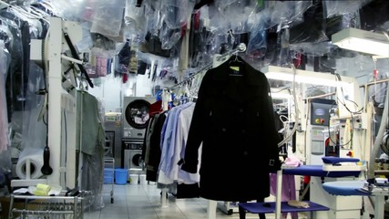 Machine work among lot of clothes in dry cleaning