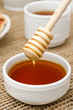 Bowl of honey with wooden dipper closeup