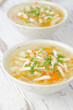 two bowls of vegetable soup with chicken and parsley