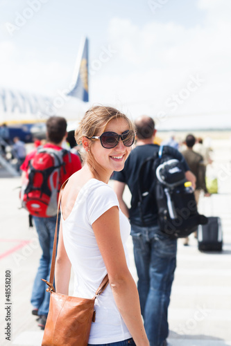 Departure - young woman at an airport about to board an aircraft