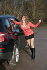 Female motorist standing by her car thumbing a lift