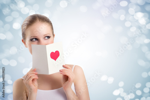 beautiful young woman holding a valentine postcard