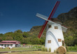 Big windmill of farm house in front of mountain