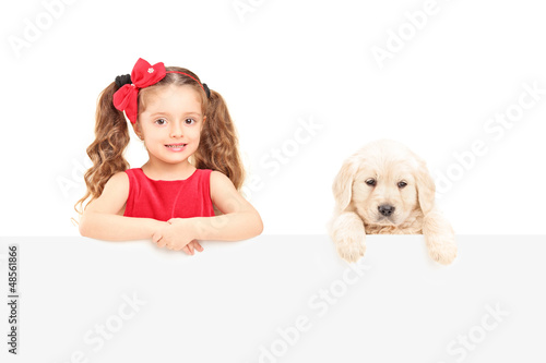 A small cute girl and labrador retriever posing behind a panel