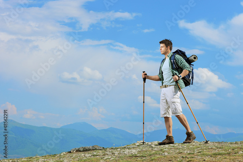 A young hiker with backpack hiking a mountain