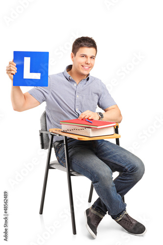 A student sitting on a school chair and holding a L plate