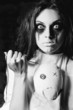 Horror scene: the strange crazy girl with moppet doll and needle