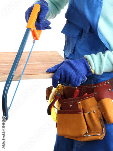 Male builder in blue overalls sawing board isolated on white