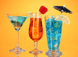 Alcoholic cocktails with ice on orange background