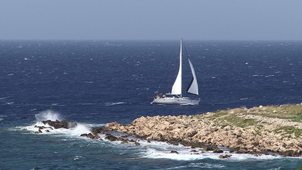 Sailboat passing by small island