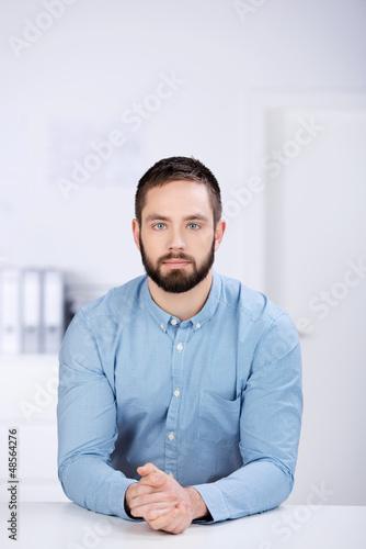 junger mann im büro schaut ernst
