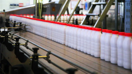 Milk bottles move on conveyor at plant