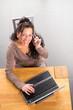 Frau telefoniert und sitzt am LapTop