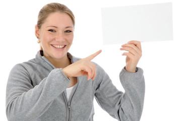 Junge Frau in grauem Freizeitanzug zeigt auf leeres Schild