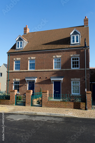 A pair of new semi-detached three storey homes with dormer windo