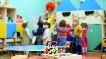 toy on table, in defocus clown blow bubbles for children