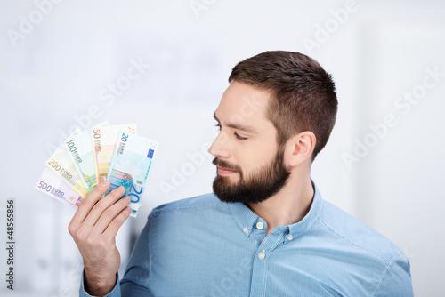 mann schaut auf geldscheine