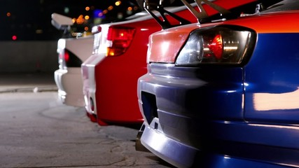 Three cars with colorful sport design at night