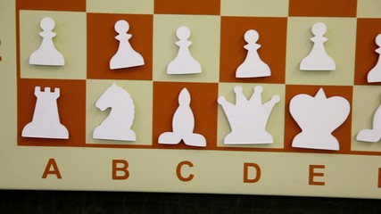 White flat chessmen at starting position on board