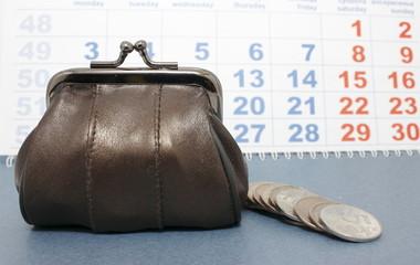 Толстый кошелек и монеты на фоне календаря